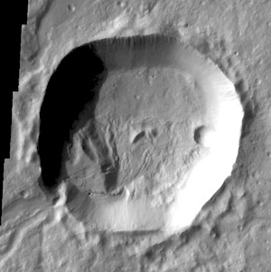 Several channels are located on the flank of Hecates Tholus. In this VIS image one of those channels enters a crater, creating a deposit on the floor of the crater. Age relationships can be derived from this image. Hecates Tholus was formed first, then the crater was created, and finally flow of lava or water carved the channel that bisects the crater rim.